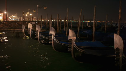 Venetian gondolas tied near the pier at night