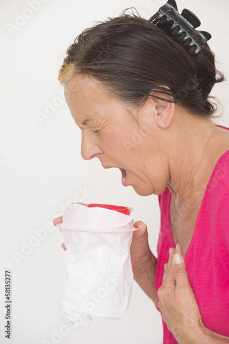 Sick woman vomiting in bag