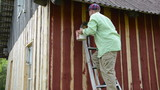 worker climb ladder to the wall paint wooden wall with red paint
