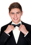 cheerful man in a black suit adjusts his bow tie