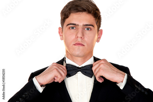 man in a black suit adjusts his bow tie close-up