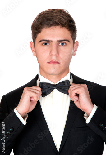 man in a black suit adjusts his bow tie