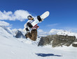 Snowboarder jumping on background of mountains