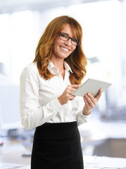 Smiling businesswoman with tablet in office