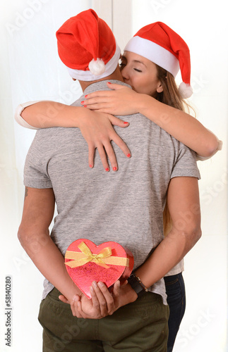 Young Couple kissing and hidden Christmas Present