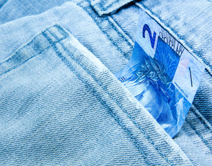 Creative composition of 2 Reais on the jeans
