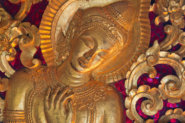 Bas-relief of golden buddha with traditional buddhism pattern