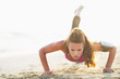 canvas print picture - Female athlete doing push ups on beach
