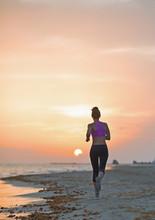 Fitness jeune femme courant sur la plage le soir. vue arrière