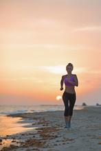 Fitness jeune femme courant sur la plage dans la soirée