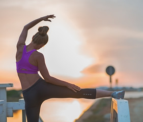 Healthy young woman stretching outdoors in the evening