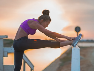 Fitness young woman stretching outdoors in the evening