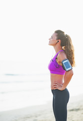 Fitness woman in headphones relaxing after running on beach