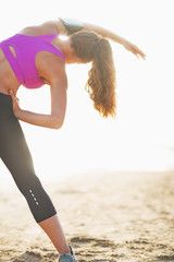 Fitness young woman stretching on beach . rear view