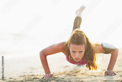 canvas print picture Female athlete doing push ups on beach