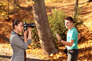 Piękna dziewczyna robi zdjęcie chłopakowi, jesienią.
