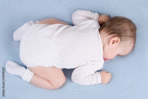 Baby sleeps on soft blue blanket. Top view
