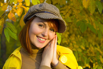 Attractive red-haired girl in the autumn wood