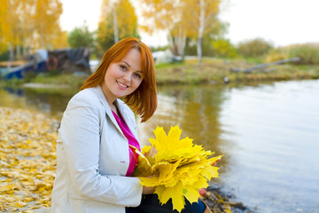 Portrait of beautiful smiling woman with maple leaves outdoors
