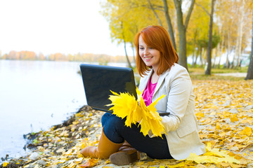 Attractive girl with laptop about a reservoir in the fall