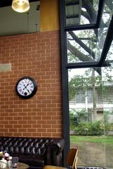 brick coffee shop seats and clock