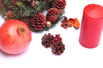 Christmas composition with red candle and pomegranate