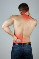 Young man touching his back and neck for the pain