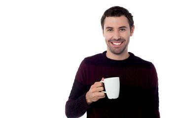 Smiling guy enjoying refreshing coffee