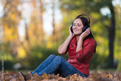 Young Girl With Headphones Enjoying Music In Autumn