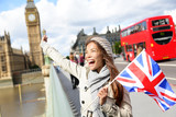 London - happy tourist holding UK flag by Big Ben