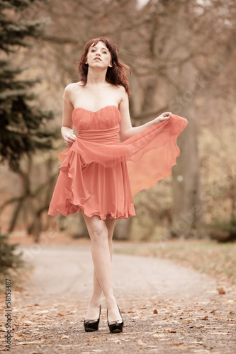 Fashion young woman in red dress relaxing in park