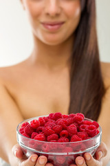 Beautiful woman holding a pot of raspberries