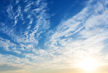 Blue sky with sun and clouds.