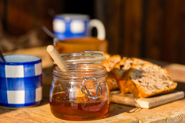 Tea, honey and fruit bread on wooden table
