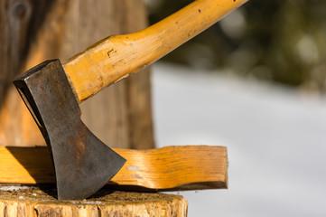 Ax stuck in block of wood winter