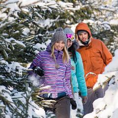 Friends walking through snow winter forest