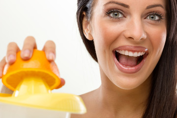 smiling young woman squeezes fresh orange juice