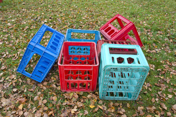 corlorful plastic boxes for beer bottles on autumn meadow