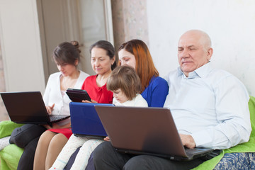 multigenerations family  with electronic devices at home