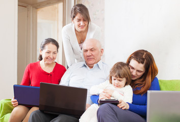 Happy multigeneration family uses few portable computers