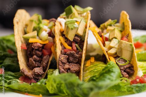 Tuinposter Kruidenierswinkel Trio of roast beef hard-shell tacos
