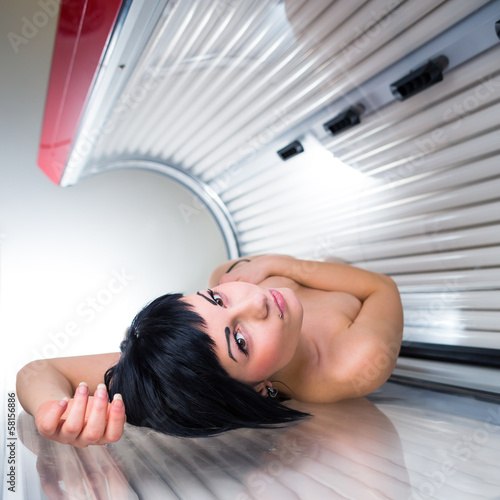 Pretty young woman tanning her skin in a modern solarium