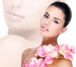 Beautiful face of  woman with healthy skin and pink flowers