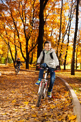 Guys riding bike in autumn park