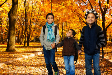 Boys go to school in autumn park