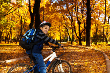 Boy with backpack on bicycle
