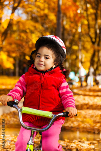 Little girl in helmet on bicycle