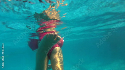A little girl swimm in pool. the camera goes under water