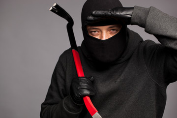 Burglar with a crowbar on the shoulder.