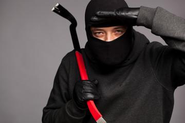 Burglar with a crowbar on the shoulder.